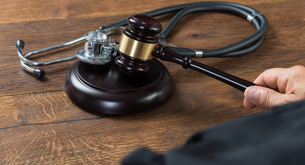 ropped image of judge hitting gavel with stethoscope in courtroom