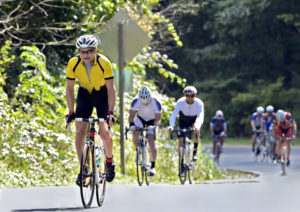 Man leading a group of riders up a mountain road during a race