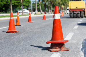 Traffic cones at tropical street warning about asphalt pavement works