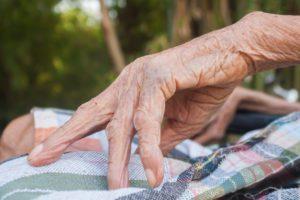 elder hand on loincloth thai, elder sitting on wheelchairs in bamboo garden