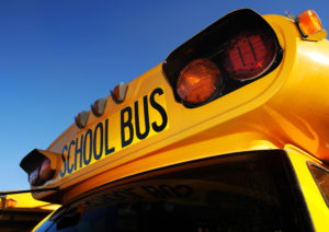 Front part of yellow school bus children educational transport with signs in the parking lot waiting to be in service