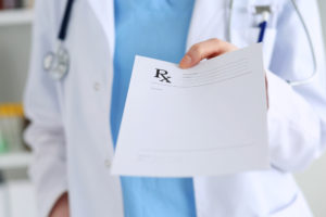 Medicine doctor hand giving prescription list to patient closeup