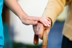 Doctor holding a senior patients 's hand on a walking stick