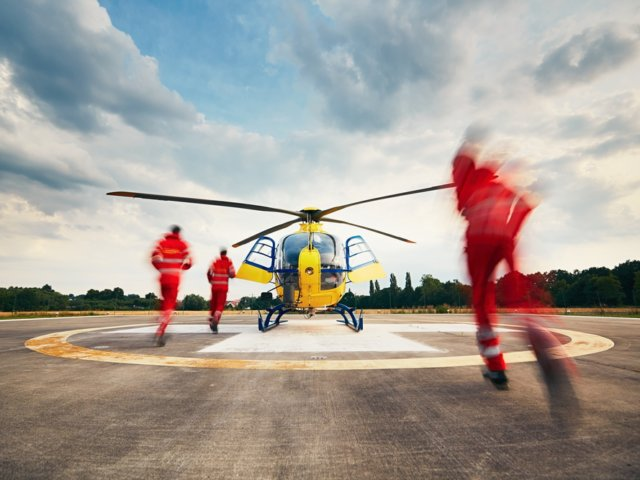 Team of rescuers (paramedic, doctor and pilot) running to the helicopter on the heliport