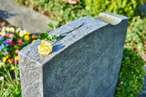 A yellow rose sits atop a gravestone