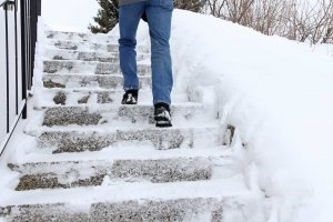 Persona carefully walks down snow-covered steps