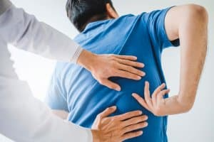 Person with back injury gets assessment from medical professional