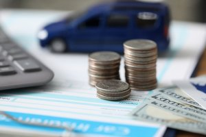 Money and toy cars sit atop a car accident settlement agreement