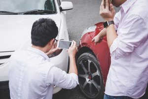 Drivers take photos of damage after a car accident